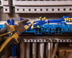 cablage d'un tableau electrique avec une pince coupante et des fils électrique
